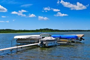 pontoon boat lift by a dock on a sunny day