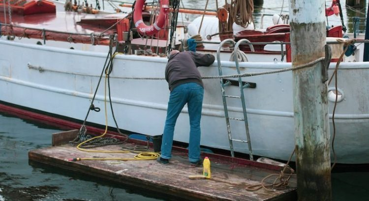 Man-cleaning-boat-in-harbor